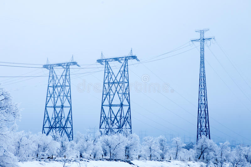 Electrical high-voltage metal pillars in winter royalty free stock photos