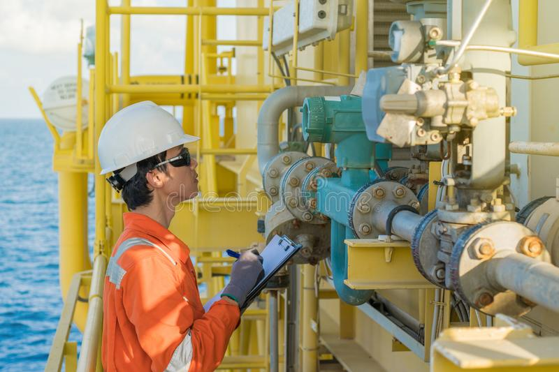 Electrical and instrument logging reading value and checking condition of oil and gas coliolis flow meter at offshore wellhead. Remote platform royalty free stock photo