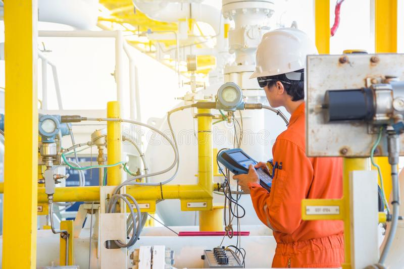 Electrical and Instrument operator calibrating temperature and pressure transmitter at offshore oil and gas central processing royalty free stock images