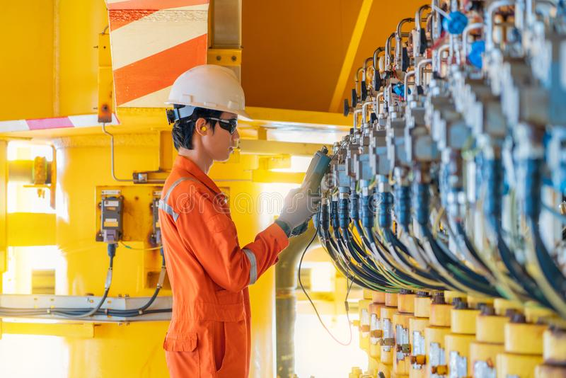 Electrical and instrument technician calibrating actuated choke valve positioner transmitter at offshore oil and gas platform. stock photo