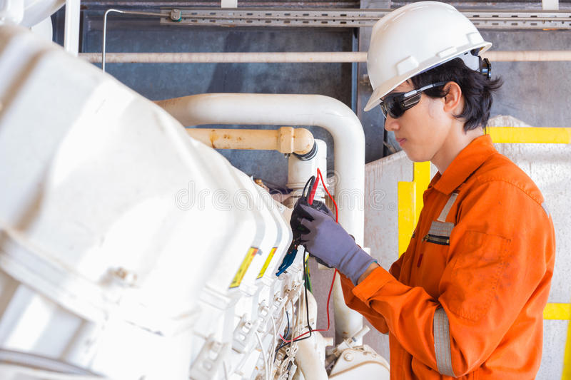Electrical and instrument technician just maintenance electric system of gas booster compressor engine at offshore platform. royalty free stock images