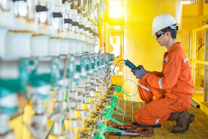Electrical and instrument technician maintenance electric system at offshore oil and gas processing platform he using hand held stock photos