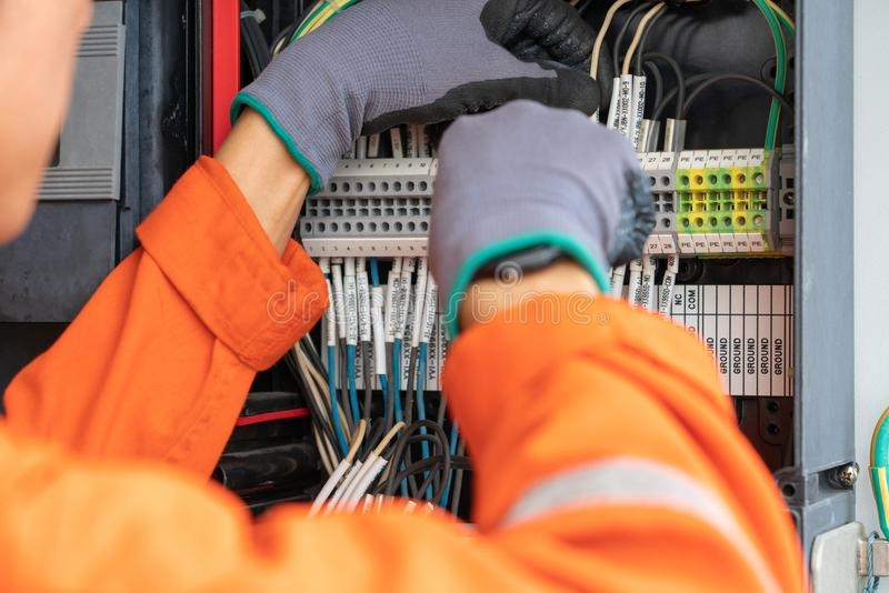 Electrical and instrument technician wiring cable at terminal and junction box. stock image