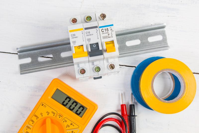 Electrical modular circuit breaker, insulating tape and digital multimeter. Electrical network protection and switching royalty free stock image
