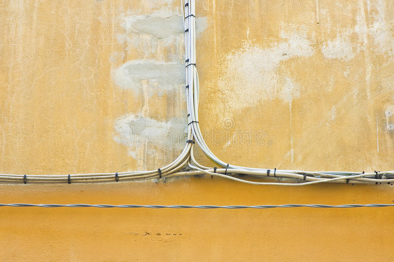 Electrical power cables against a plaster wall stock photo