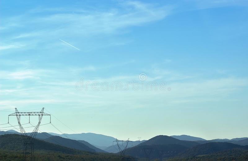 Electrical power line and pylons against mountain landscape royalty free stock images