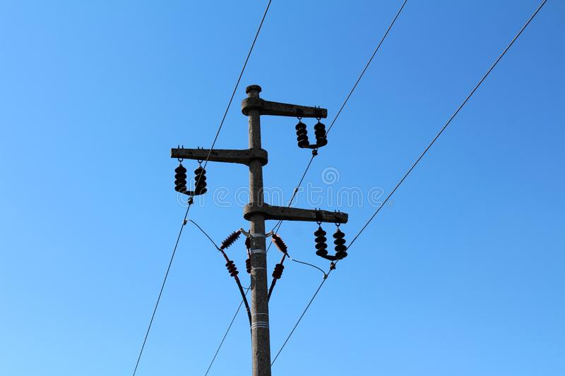 Electrical power line utility pole made of strong concrete with multiple ceramic insulators connecting and holding wires royalty free stock photo