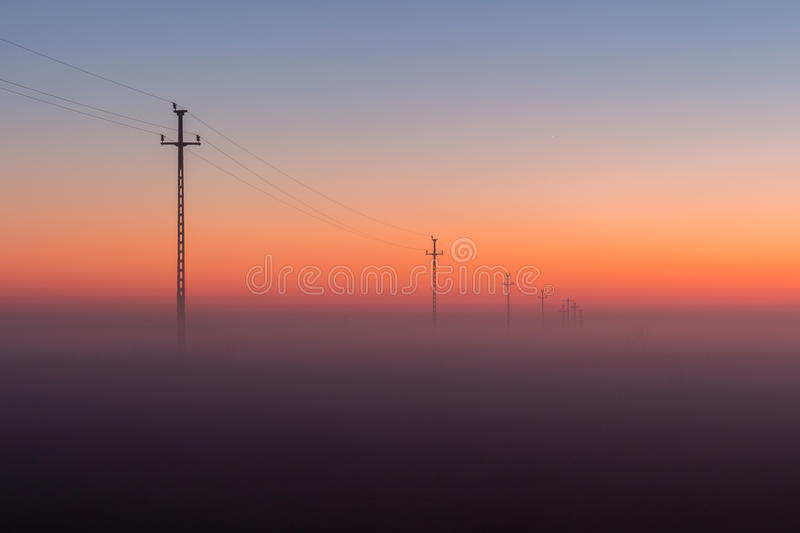 Electrical Power Lines and Pylons disappear over the horizon with Misty Sunrise, Sunset.  royalty free stock photos