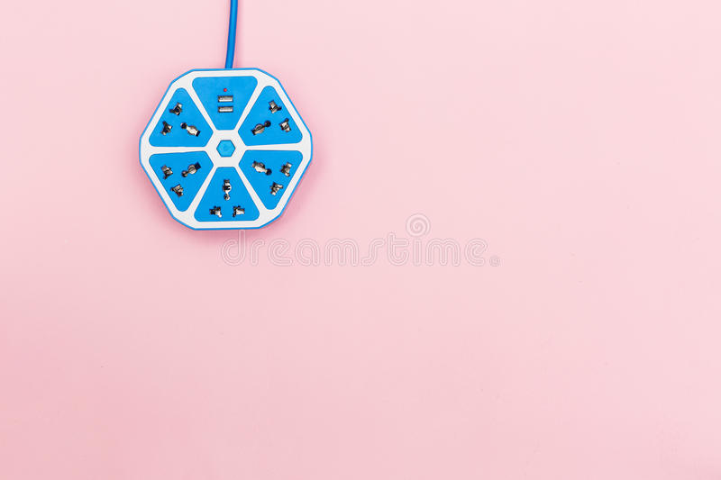 Electrical power strip color blue hexagon model on pink background, view from above. royalty free stock photography
