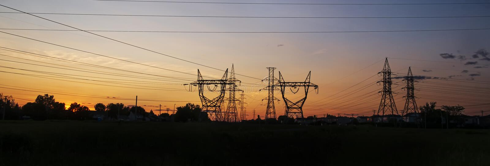 Electrical power towers at sunset. A bunch of electrical transmission towers electricity pylons carrying high voltage lines in the city at sunset stock photo