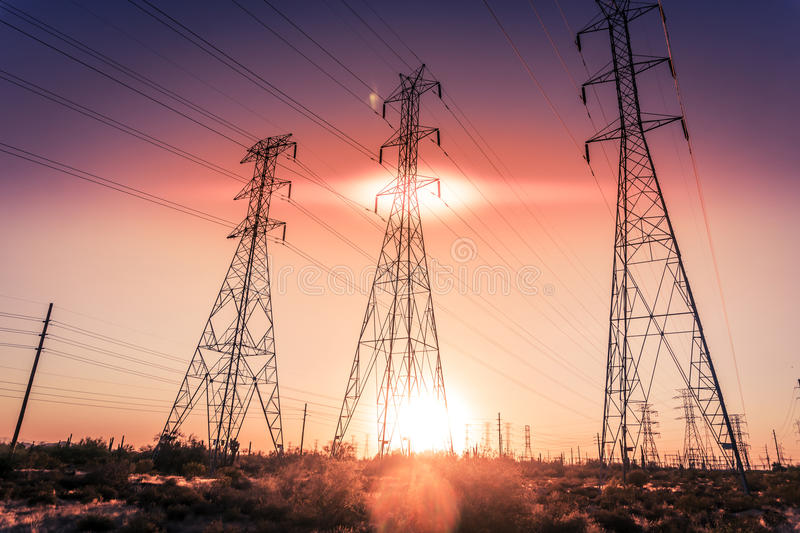 Electrical power transmission towers. As sun sets royalty free stock image