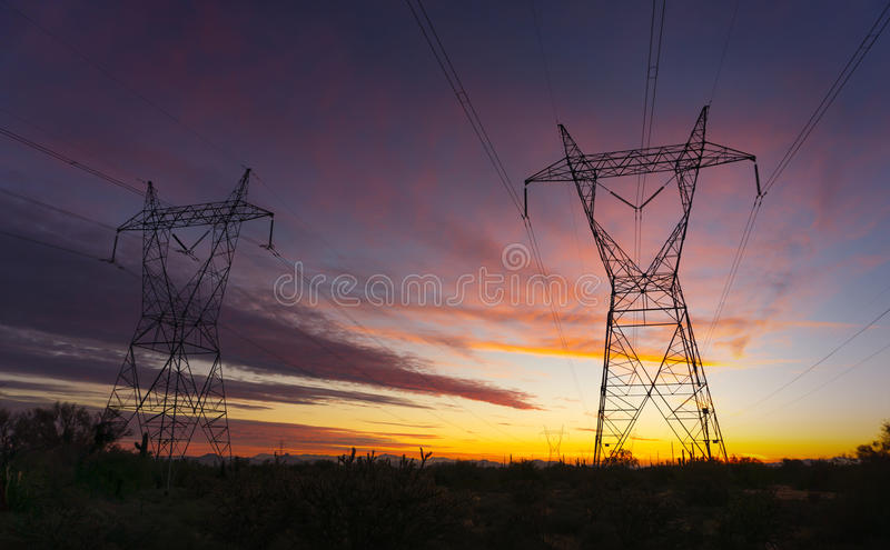 Electrical power transmission towers. Over the desert in Arizona at Sunset stock photo