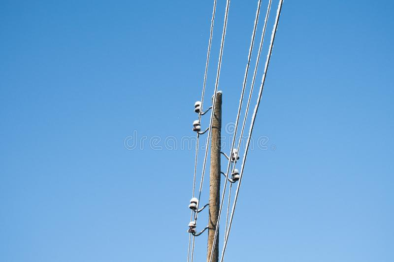 Electrical powered pillar under the snow in blue sky. Outdoor view royalty free stock photos