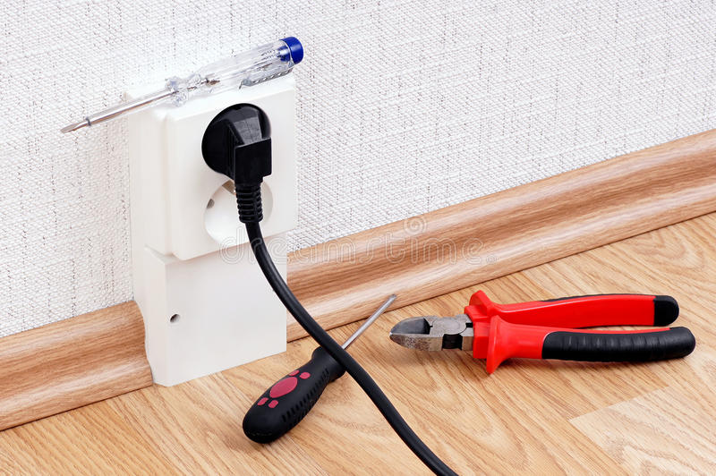 Electrical socket and tools. Electric socket with connected cable and tools- Electric current tester,pliers and screwdriver royalty free stock images