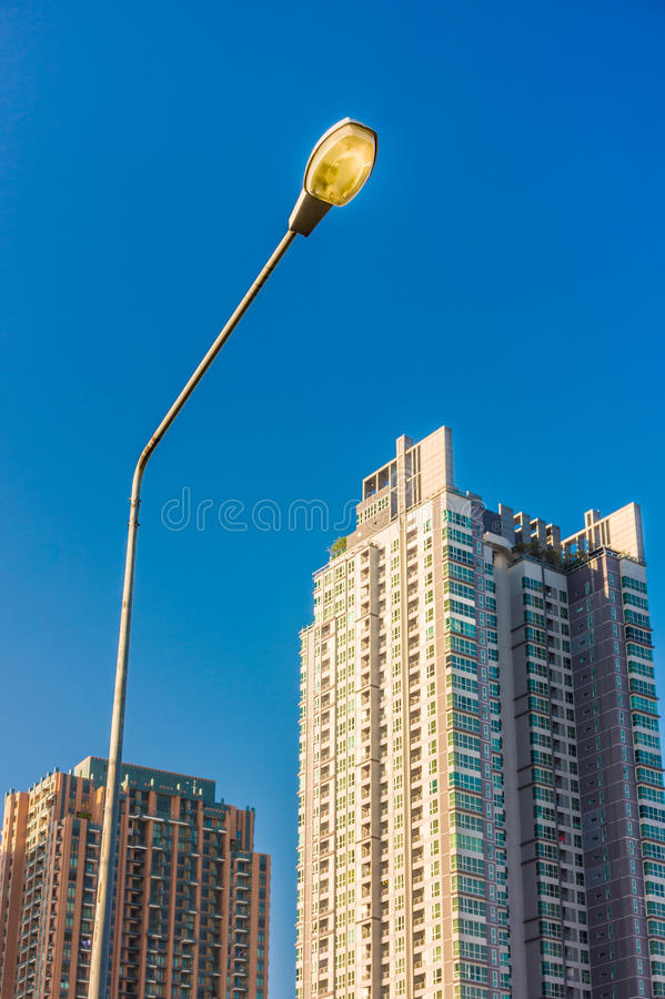 Electrical streetlamp with high rise modern building background. The lighting system in Bangkok city, Thailand stock image