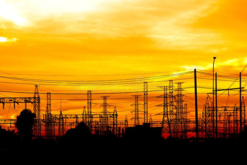 Electrical substation and high voltage ac transmission towers against the sunset. Power transmission towers line silhouetted royalty free stock image