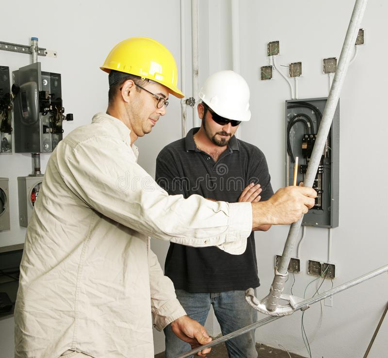Electrical Team Bending Pipe. Electrician and foreman bending pipe for a job. Actual electricians working according to industry safety and code standards. ( royalty free stock photos
