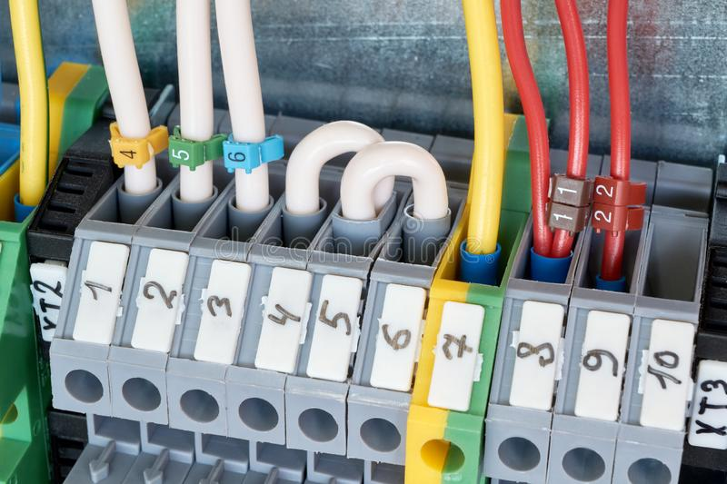 Electrical terminals with wires connected to them in the electrical Cabinet. Electrical terminals with connected wires are installed in a row in the electrical stock photo