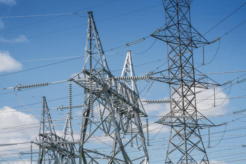 Electrical towers details. Electrical towers and wires on a blue sky stock image