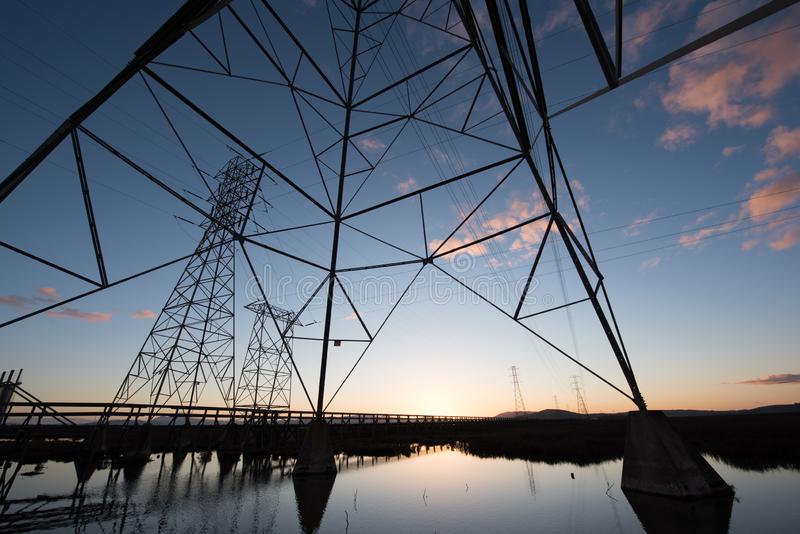 Electrical towers with leading lines at sunset, with reflections in water. Multiple electrical towers with criss crossing cables leading off to the horizon. At stock photos