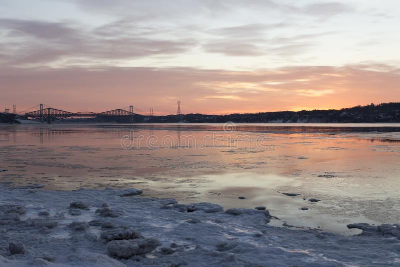 Electrical towers, Pierre-Laporte and Quebec bridges over the St. Lawrence river. Seen in the distance during a beautiful winter sunrise, Cap-Rouge area, Quebec stock photos