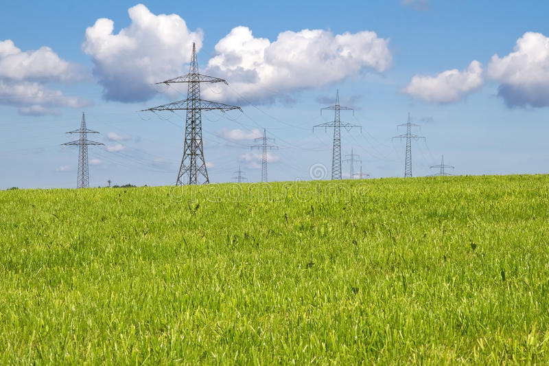 Electrical towers on a spring meadow royalty free stock image