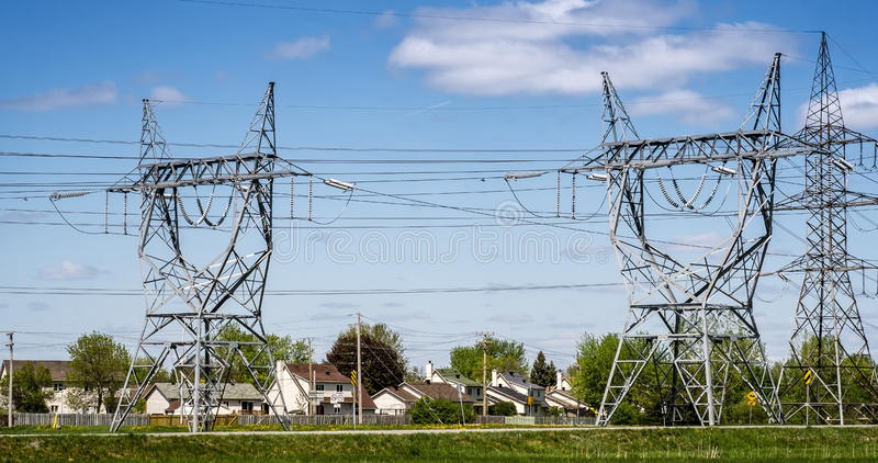Electrical towers. And wires in a residential area on a blue sky royalty free stock image