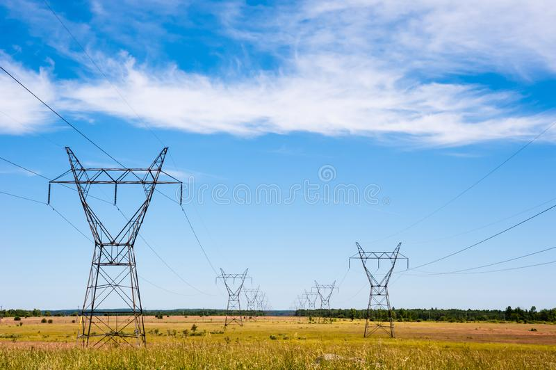 Electrical transmission towers and power lines on fields stock image
