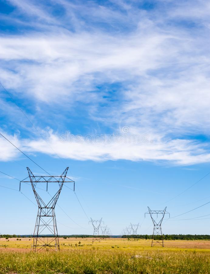 Electrical transmission towers and power lines on fields. Large electrical transmission towers and power lines receding into distance on rural fields under royalty free stock photo