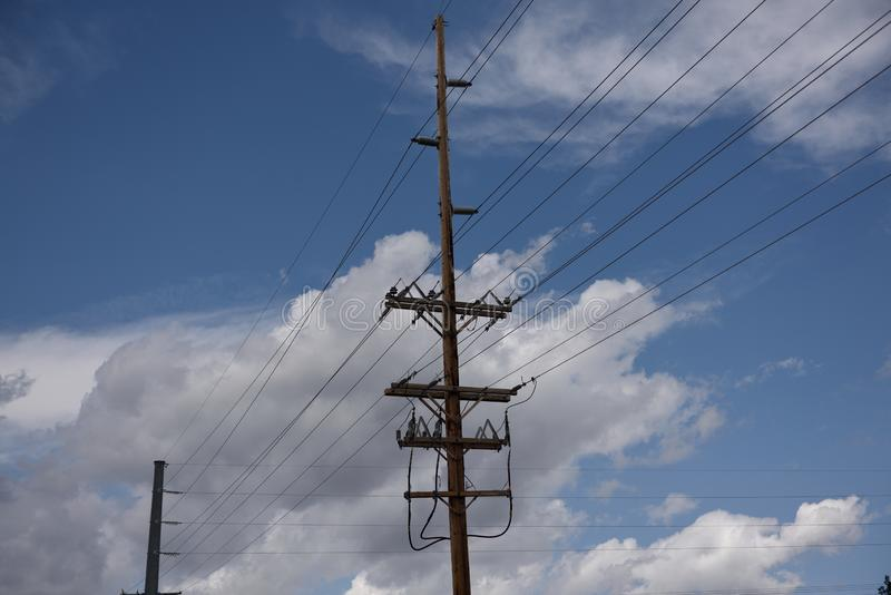 Electrical utility poles and overhead high voltage power lines against a blue sky and clouds. In Wyoming stock images