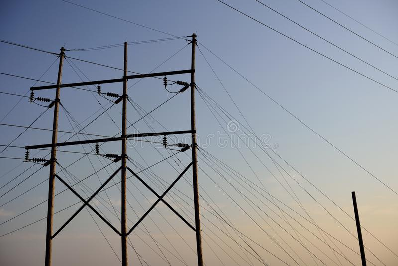 Electrical utility poles and overhead high voltage power lines at sunset royalty free stock photo