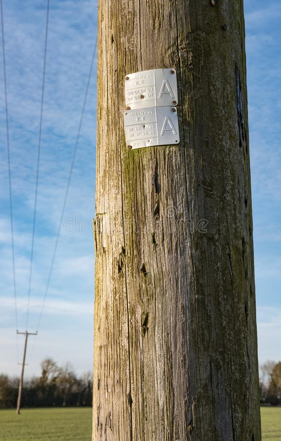Electrical utility poles seen carrying high-voltage cables to a small english village. royalty free stock photography