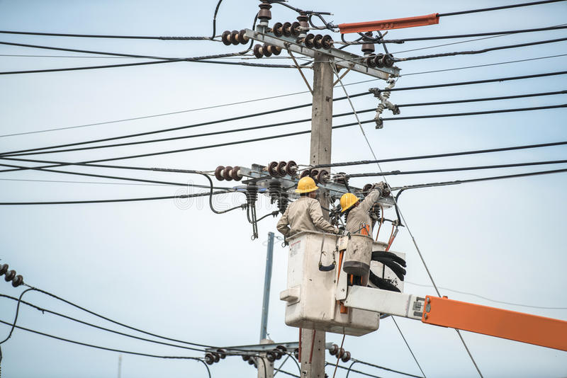 Electrical utility worker in a bucket fixes a problem with a power line. stock images