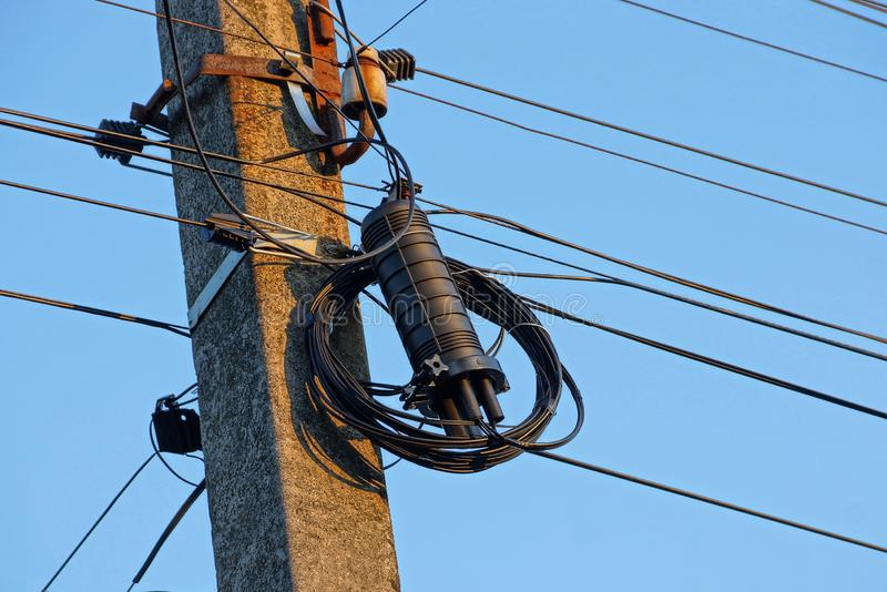 Electrical wires and black box on a gray concrete pillar royalty free stock photography
