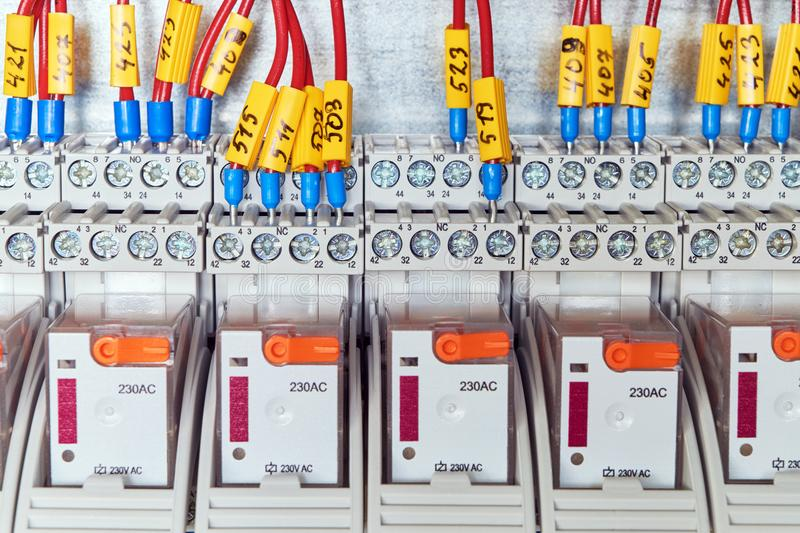 The electrical wires or cables are connected to an intermediate relay according to the scheme. stock photo