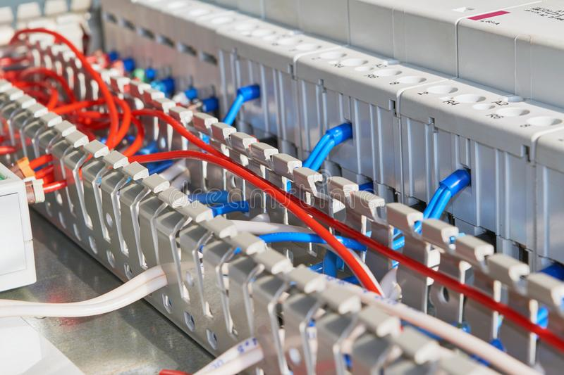 Electrical wires or cables are laid in a perforated protective channel. The wires are connected to electric modular contactors with insulated terminals stock photography