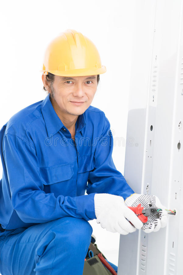 Electrician. Vertical shot of a professional electrician doing maintenance work stock photo