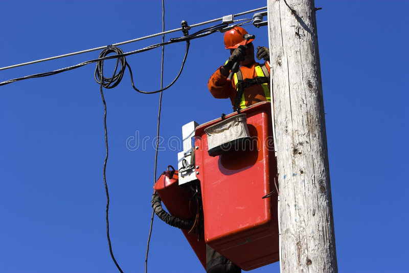 Electrician. In a cherrypicker working on installing overhead wires royalty free stock images