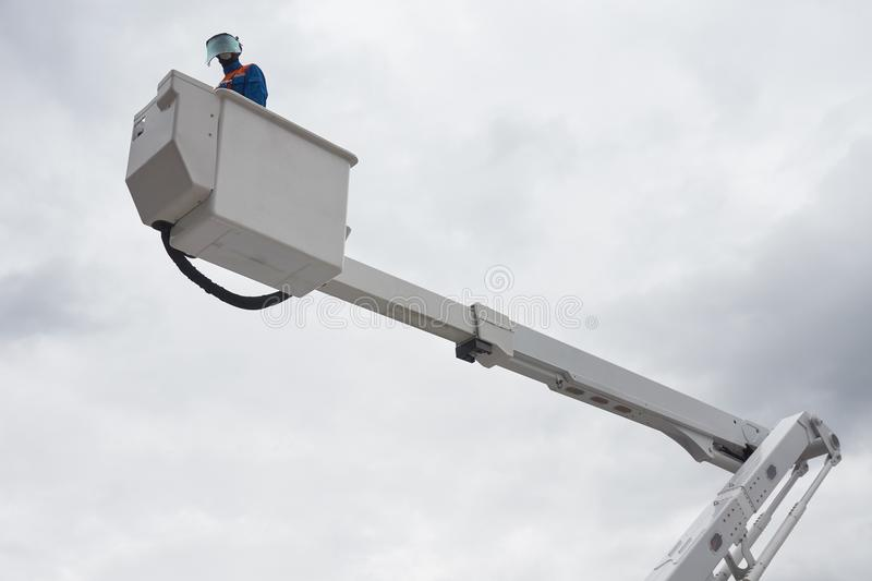 An electrician on aerial platform. An electrician in protective uniform works on insulated aerial platform designed to work safely on electric power lines stock photo