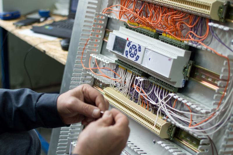 Hands of electrician assembling industrial HVAC control box in workshop. Close-up photo. royalty free stock photography