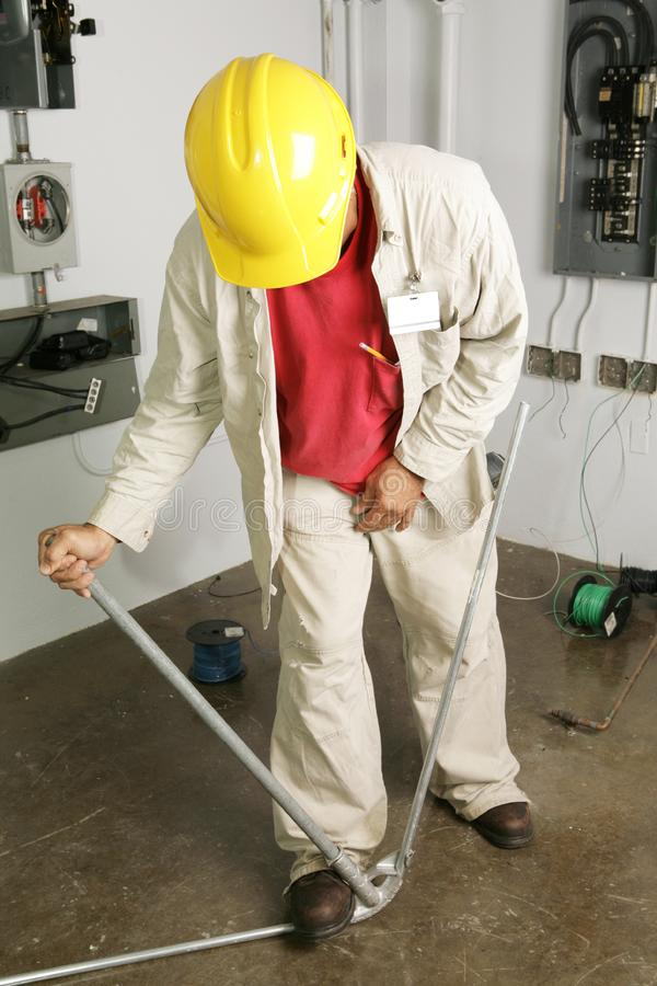 Electrician Bends Pipe. Electrician bending conduit pipe. Actual electrician performing work according to industry code and safety standards. (writing on pipe is royalty free stock images