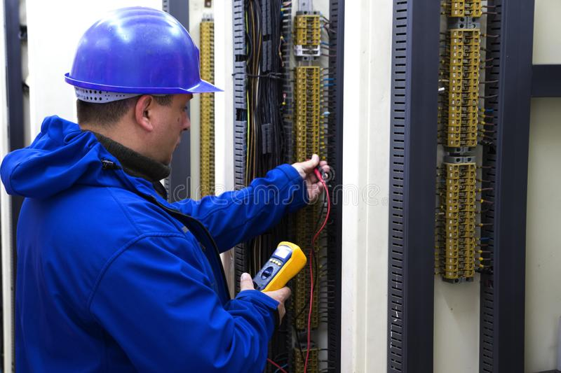 Electrician in blue control circuit with multimeter. Worker in blue helmet make electrical measurements stock image