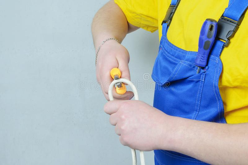 Electrician in a blue jumpsuit and a yellow T-shirt, trying to cut the wire. Man at work. stock photography