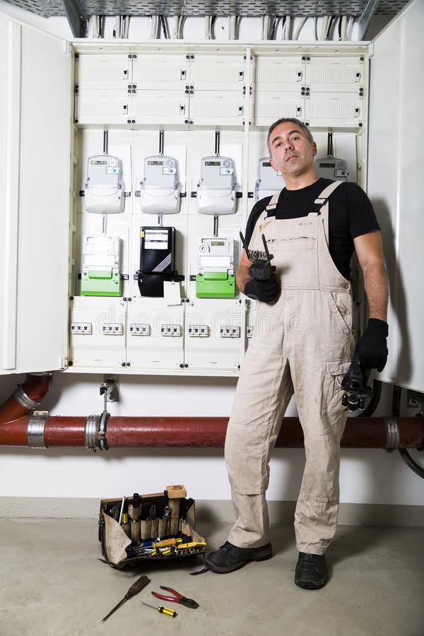 Electrician with box of tools standing near distribution board stock photography