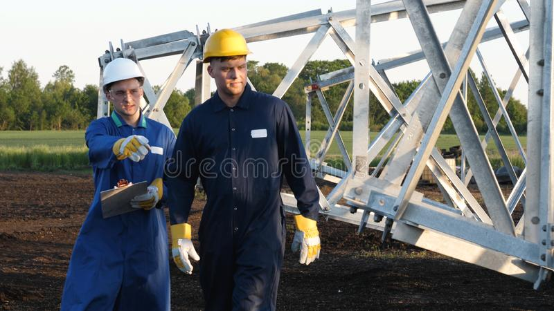 An electrician or builder and engineer, in a blue robe, in a yellow and white helmet, check the technical overview for strength, p. Repare electric poles, an royalty free stock photos