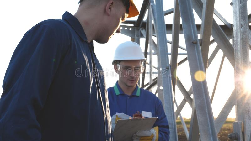 An electrician or builder and engineer, in a blue robe, in a yellow and white helmet, check the technical overview for strength, p. Repare electric poles, an stock photography