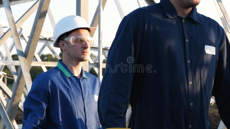 An electrician or builder and engineer, in a blue robe, in a yellow and white helmet, check the technical overview for strength, p. Repare electric poles, an royalty free stock photography
