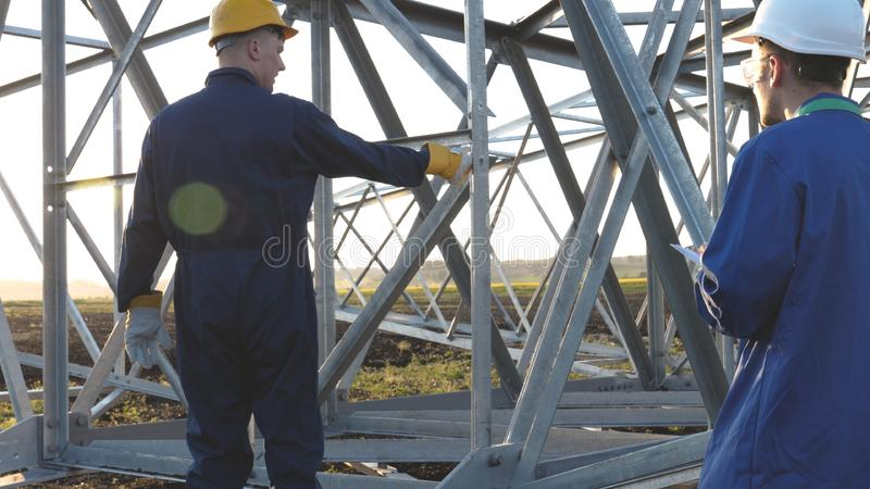 An electrician or builder and engineer, in a blue robe, in a yellow and white helmet, check the technical overview for strength, p. Repare electric poles, an stock photos