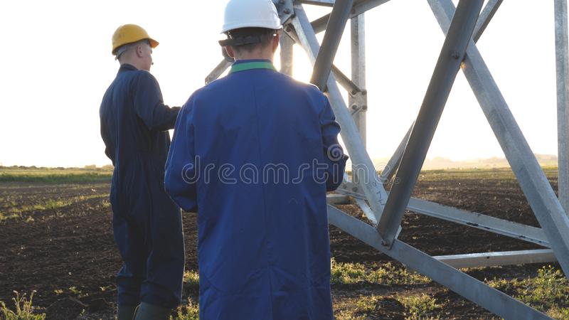An electrician or builder and engineer, in a blue robe, in a yellow and white helmet, check the technical overview for strength, p stock images
