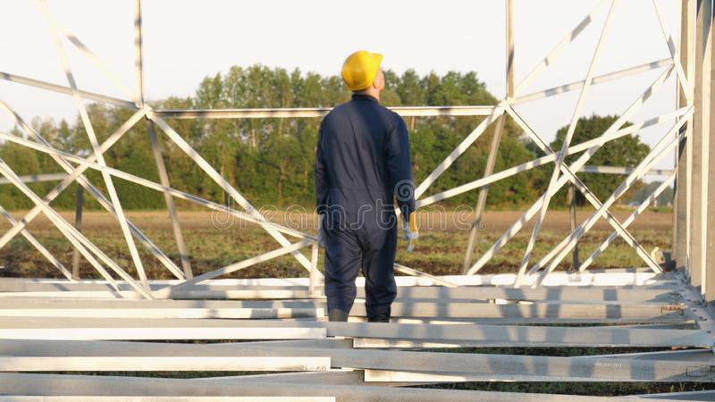 An electrician or builder and engineer, in a blue robe, in a yellow and white helmet, check the technical overview for strength, p. Repare electric poles, an royalty free stock photo